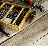 Drills in box, drill, chisel on a wooden background. — Stock Photo
