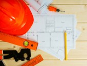 Repair work. Drawings for building, helmet, pencils and others tools on wooden background. — Stock Photo