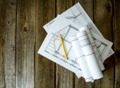 Many drawings for building and pencils on old wooden background. — Stockfoto