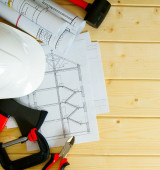 House construction. Drawings for building, helmet and others tools on wooden background. — Stock Photo