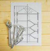 Drawings for building and metal working tools on wooden background. — Stock Photo