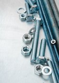 Metal hairpins and bolts on the scratched metal background. — Stock Photo