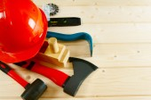 Helmet, mount, axe, plane and other tool on a wooden background. — Stock Photo
