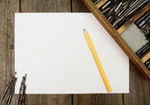 Paper with pencil and box, drills on wooden background. — Stock Photo