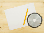 The Sheet of paper with pencil and circle saw on wooden background. — Stock Photo