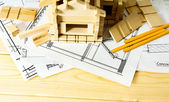 Many drawings for building, pencils and small house on wooden background. — Stock Photo
