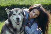 Beautiful woman with Malamute dog — Stock Photo