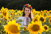 Beautiful young girl at sunflower field — Stock Photo
