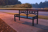 Bench near the road — Stock Photo