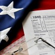 Tax form on american flag — Stock Photo #64162559