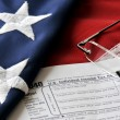 Tax form on american flag — Stock Photo #64162683