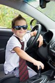 Cute driver in sunglasses and tie sits in car — Stock Photo