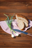 Rye bread, onion and knife on wood, outdoor. Focus on onion — Fotografia Stock