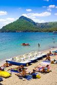 FORMENTOR, MALLORCA - AUGUST 22, 2014: Tourists on beach. Sea bay turquoise water mountain view , Cala Pi de La Posada, Cap Formentor, Majorca, Spain — ストック写真