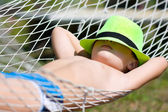 Happy boy in  hammock at garden. Focus on hat — Stock Photo