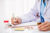 Doctor writing medical record — Stock Photo