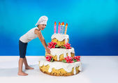 Little confectioner drags a cake — Stock Photo