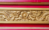 Golden dragon decorated on red wood wall — Stock Photo