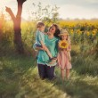 Mother with children in sunflowers — Stock Photo #63420921