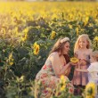 Mother with children in sunflowers — Stock Photo #63421009