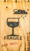Glass icon of fragile item spray on brown plywood tex — Stock Photo