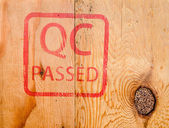 Stamp QC PASSED on wood background — Stock Photo