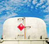 Backside of oil truck car with measure check level oil on blue s — Stock Photo