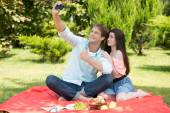 Happy romantic couple taking pictures at picnic — Stock Photo