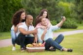 Happy friends taking pictures at picnic — Stock Photo
