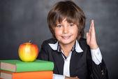 Happy school boy with raised hand — Stock Photo