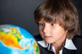 Interested school boy with globe — Stock Photo