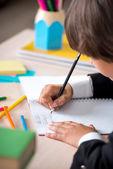 School boy writing in notebook — Stok fotoğraf