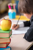 Close-up of apple with school boy behind — Stock Photo