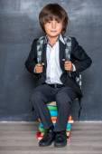 School boy sitting on books — Stock Photo