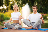Young couple maditating in lotus pose — Stock Photo