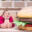 Smiling overweight woman and huge hamburger — Stock Photo #57007317