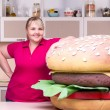 Smiling overweight woman and huge hamburger — Stock Photo #57007333