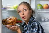 Girl holding fried chicken near opened refrigerator — Stock Photo