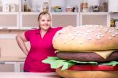 Smiling overweight woman and huge hamburger — Stock Photo