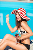 Happy young woman waffing and sitting close by swimming pool — 图库照片