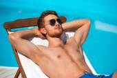 Young man relaxing on chaise longue — Stock Photo