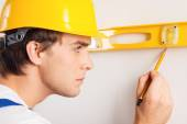 Close-up of repairman measuring with builder level — Stock Photo