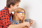 Smiling repairman helping woman to use drill — Stock Photo