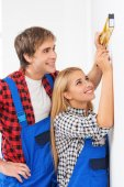 Repairman helping woman to use builder level — Stock Photo
