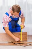 Repairman measuring wood block — Stock Photo