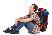 Smiling hiker sitting with knapsack — Stock Photo