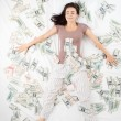 Happy woman sleeping in a bed full of money — Stock Photo #63665543
