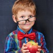 Mixed-up ginger primary school age boy holding red apple — Stock Photo #64746405