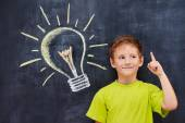 Handsome ginger schoolboy standing in front of a blackboard — Stock Photo