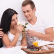 Man giving rose to his wife while having breakfast in bed — Stock Photo #65046695